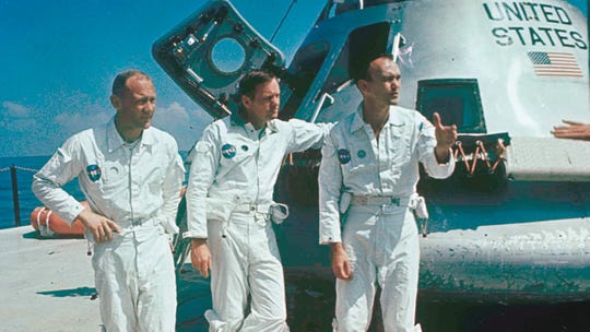 Apollo 11 astronauts stand next to their spacecraft in 1969, from left to right:  Col. Edwin E. Aldrin, lunar module pilot; Neil Armstrong, flight commander; and Lt. Michael Collins, command module pilot.