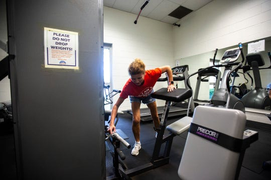 Courtney Bender works out with weight machines, Wednesday, July 17, 2019, at the Recreation Center in Coralville, Iowa.