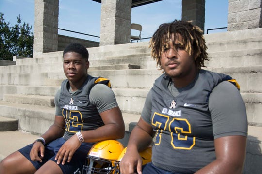 Jevon Banks and Xavier Hill of Olive Branch High School take a break during summer practice.