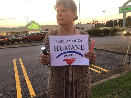 With a flashlight and a sign, a community member stands on the sidewalk outside of Old Hickory Mall to protest detention centers.