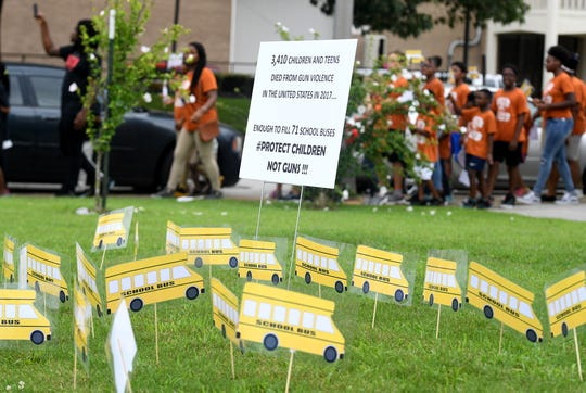 Freedom School students march around Mother Liberty CME Church to bring awareness to gun violence in the country, Wednesday, July 17. A display of school busses are posted in the lawn of the church to illustrate how many children died from gun violence in 2017.