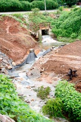 """The Fourth Creek spills out from a tunnel behind the IHOP on Kingston Pike on Wellington Drive in West Knoxville, Tennessee on Wednesday, July 17, 2019. Erosion by the Fourth Creek has created a 130-foot-wide 30-foot-tall chasm, known as Knoxville's """"Grand Canyon."""""""