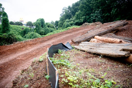 """Construction work begins on the eroded section of the Fourth Creek behind the IHOP on Kingston Pike on Wellington Drive in West Knoxville, Tennessee on Wednesday, July 17, 2019. Erosion by the Fourth Creek has created a 130-foot-wide 30-foot-tall chasm, known as Knoxville's """"Grand Canyon."""""""