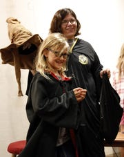 """Lily Hawkins, 9, from Lancaster smiles as she walks away from the sorting hat with red stone symbolizing that she belongs to the Gryffindor house at Hogwarts School of Witchcraft and Wizardry last year, at the Fairfield County District Library in Lancaster. Becky Schaade, right, the library's director was leading the sorting for the 20th anniversary of the """"Harry Potter"""" series. This year's Potter event will be Aug. 1-3 and will be called Wands & Wizards Weekend."""