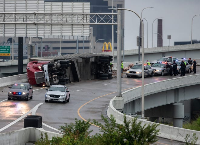 A tractor trailer lays on its side on the southbound I-65 ramp to eastbound I-64 and I-71. The truck was hauling a load of pigs. July 17, 2019.