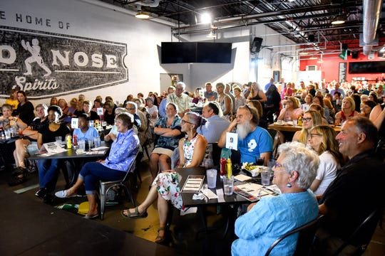 Guests listen as Lily Werbin speaks on stage during the Lansing Storytellers Project: 'Growing Pains' event on Tuesday, July 16, 2019, at the Lansing Brewing Company.