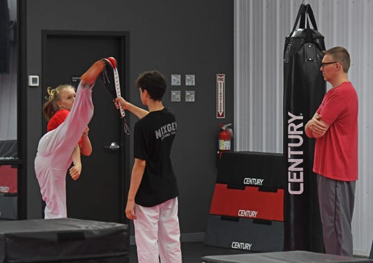 Chris Hershberger, who runs Black Belt Pro Fitness and the NexGen Taekwondo Team, watches his daughter Natalie train.
