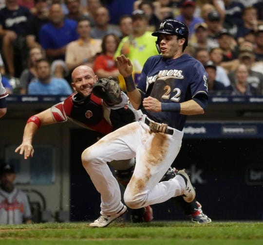 Brewers right fielder Christian Yelich scores on a wild pitch in the fifth inning, eluding the tag of Braves catcher Tyler Flowers.