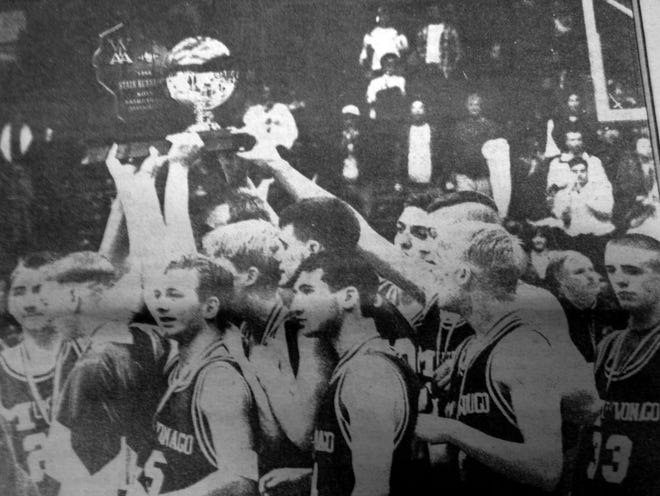 the 1996 Mukwonago boys basketball team hoists its runner-up trophy from the Division 1 state tournament