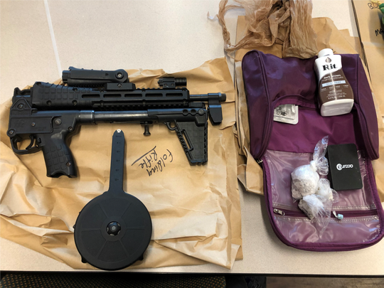 A semi-automatic rifle and bags of seized drugs are seen in photos provided by the U.S. attorney for the Eastern District of Wisconsin. Authorities recovered 24 guns, 5 kilograms of cocaine and 1 kilogram of heroin while serving warrants Tuesday across Milwaukee.