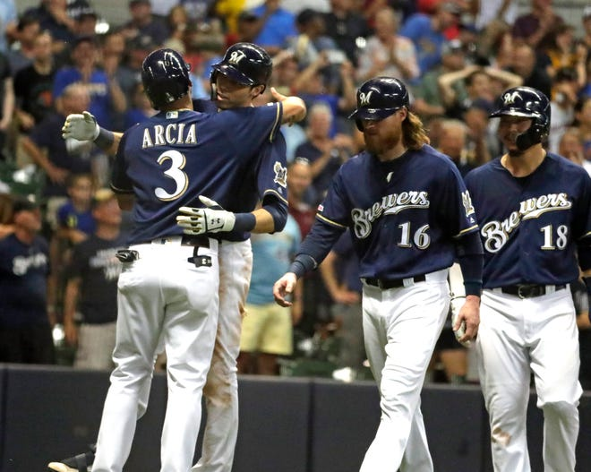Christian Yelich gets a hug from Orlando Arcia after belting a grand slam in the seventh inning which gave the Brewers a 10-run cushion over the Braves.