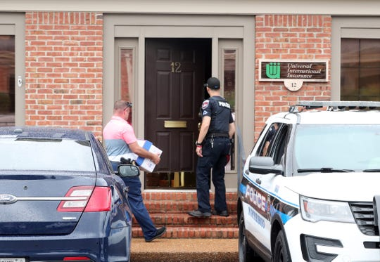 Murfreesboro police Det. David Harrison brings boxes in as Officer Hector Montalvo opens the door at Universal International Insurance, the office of Rutherford County Mayor Bill Ketron, during a police raid on July 17, 2019.