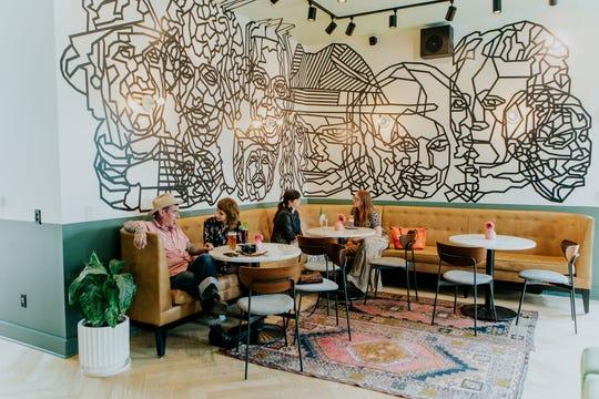 Lounge area underneath Dustin Hedrick's mural at Vandyke Bed & Beverage.