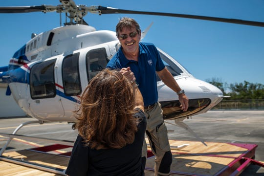 Pilot Mike Berkitsch, right, cheers with Robin King, spokeswoman for Collier Mosquito Control District, after the landing on Wednesday, July 17, 2019. The new helicopter will replace two older aircraft used for aerial spraying missions to combat mosquitoes.