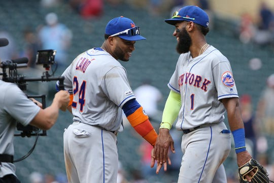 New York Mets' Amed Rosario celebrates with teammate Robinson Cano after winning 14-4 against the Minnesota Twins during a baseball game Wednesday, July 17, 2019, in Minneapolis. (AP Photo/Stacy Bengs)