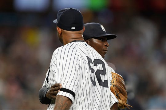 New York Yankees' Didi Gregorius, right, restrains Yankees starting pitcher CC Sabathia during the sixth inning of the team's baseball game against the Tampa Bay Rays, Tuesday, July 16, 2019, in New York. Sabathhia and Rays' Avisail Garcia had words, then benches and bullpens cleared. (AP Photo/Kathy Willens)
