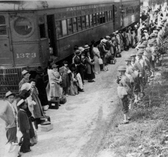 People of Japanese descent line up for a train that will take them from the Santa Anita assembly camp in California to an internment camp at Gila River, Ariz. in 1942. U.S. soldiers face them, right. The internment of Japanese during World War II required the suspension of civil rights for the minority group.