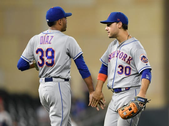 Edwin Diaz and Michael Conforto of the New York Mets celebrate defeating the Minnesota Twins after the interleague game on July 16, 2019 at Target Field in Minneapolis, Minnesota. The Mets defeated the Twins, 3-2.