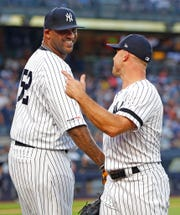 New York Yankees' starting pitcher CC Sabathia (52) laughs and smiles with Yankees' left fielder Brett Gardner who nade a spectacular catch to rob the Tampa Bay Rays of a home run in a baseball game, Tuesday, July 16, 2019, in New York.