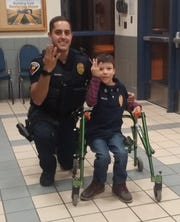 "Las Cruces Police Officer Jason Sauceda and Jacob Avalos pose after Jacob spent a day with the police department. The four-fingers mean ""10-4"" or ""everything's OK."""
