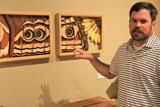 Curator Jeffrey Richardson discusses a detail in a triptych by Steven Barr in an exhibition of the artist's work at the Farmington Museum at Gateway Park.
