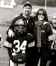 Drew Poet is pictured with his parents, Kevin and Mary, prior to a Plymouth-Canton Steelers game.