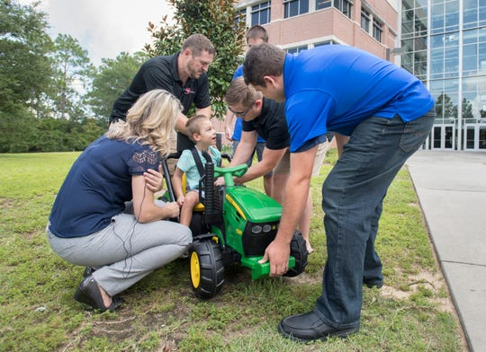 4-year old Jack Carroll looks up at the UWF engineering students as they help him into a vehicle that they modified for him at University of West Florida's Hal Marcus College of Science and Engineering in Pensacola on Wednesday, July 17, 2019.  The modified vehicle will help Jack's mobility that is reduced due to celebral palsy.