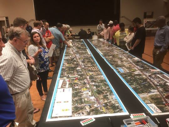 Pensacola residents review the details of a proposed pedestrian safety project that would reduce lane widths and add lighting and raised medians to West Cervantes Street.