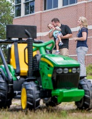 4-year-old Jack Carroll is all smiles as his parents Mike and Danielle talk about the specially modified vehicle make by engineering students at University of West Florida's Hal Marcus College of Science and Engineering in Pensacola on Wednesday, July 17, 2019.  UWF engineering students modified the vehicle to help Jack's mobility that is reduced due to celebral palsy.
