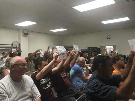 "North Codorus Township community members hold up signs stating, ""The people vote 'no,'"" when the supervisors motioned to vote on the ordinance adopting a policing agreement with Northern York County Regional Police Department on July 16, 2019."
