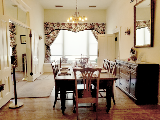 Situated mid-home between the butler's pantry and living room, the dining room is dressed in fine furnishings, china and glassware.