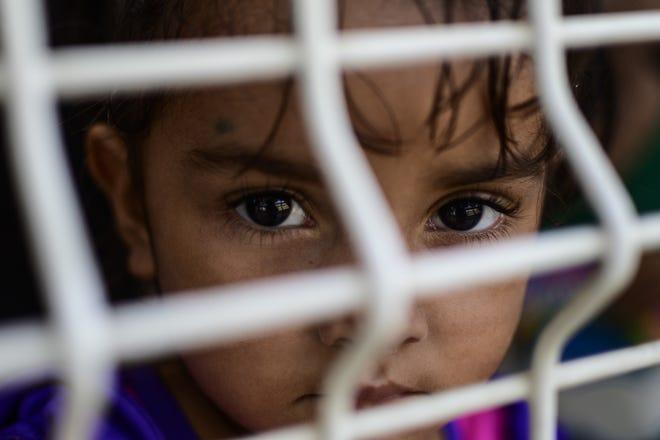 Una niña migrante espera junto a su familia por una visa humanitaria en México.