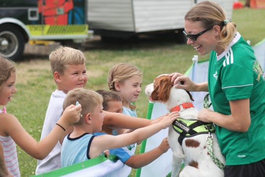 Megan Builderbeck, right, of Team ZOOM, and canine star, Hopper, greet some spectators at the Ottawa County Fair.