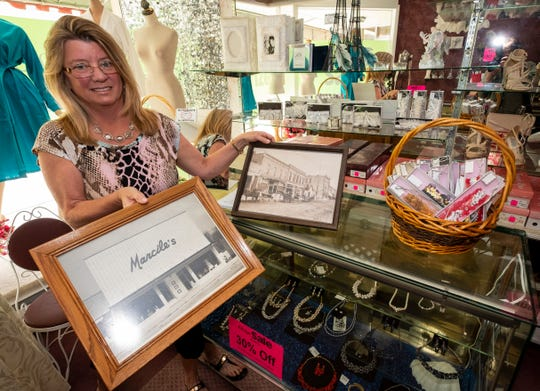 Sally Like, co-owner of Marcile's Fashion and Bridal, holds a photo of the storefront after being remodeled in 1964, near one of the store's jewelry display cases Tuesday, July 16, 2019. After about 60 years, the Richmond store is closing.