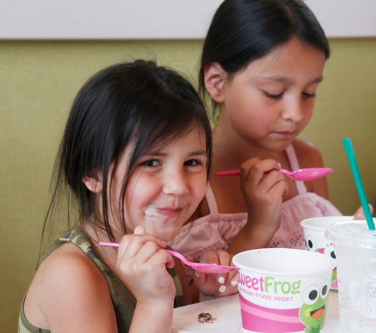 Mia and Aliyah Perry of Wappingers Falls enjoy a cold treat at Sweet Frog Frozen Yogurt in the Town of Poughkeepsie on July 17, 2019.