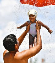Navishaa Gowri, 1, is held under a cool shower of water by her father Naveen Kumar, of Springettsbury Township, as the heat index reaches 100 degrees at the Red Lion Splash Pad in Fairmount Park, Wednesday, July 17, 2019. Dawn J. Sagert photo