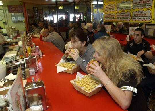 Back in the day, jaw stretching commences to accommodate Awful Awful burgers at the diner in the Little Nugget casino in downtown Reno.