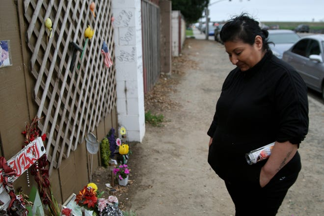 Lenore Sosa stares at the memorial for her son. May 2019.