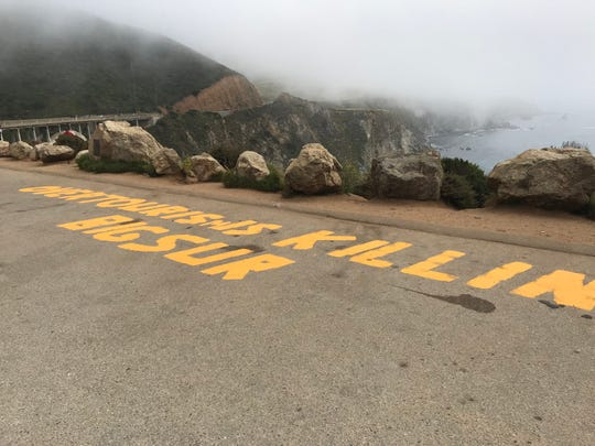 A photo of the graffiti message on the asphalt parking lot with the Bixby Bridge in the background. July 17, 2019.