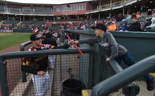 Delmarva Shorebirds' outfielder Robert Neustrom interacts with a young fan at Arthur W. Perdue Stadium.