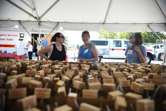 Lisa Ludwig smiles under the white tent holding the memorial mallets and glasses that guests continue to scoop up  at the 43rd Annual Tawes Crab and Clam Bake continues to grow in Crisfield, Maryland, on July 17, 2019.