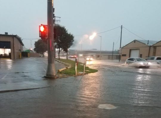 Cars drive through the flooded intersection of 54th Street and Cliff Avenue after heavy rain caused flash flooding in Sioux Falls, South Dakota on July 17, 2019.
