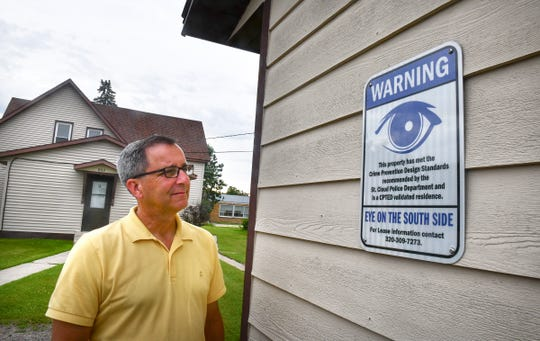 Brian Murphy stands next to an Eyes on the South Side sign posted on one of the rental properties he owns Wednesday, July 17, 2019, in St. Cloud.