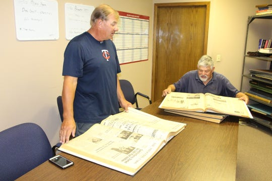 Brian Dorr (left) and Luther Dorr look over bound volumes of old Princeton Union-Eagle newspapers in preparation for this weekend's 50th Annual Princeton American Legion Baseball Tournament. The tournament starts Friday.