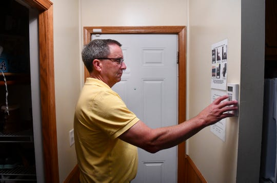 Brian Murphy activates the security system on an Eyes on the South Side certified property he owns Wednesday, July 17, 2019, in St. Cloud.