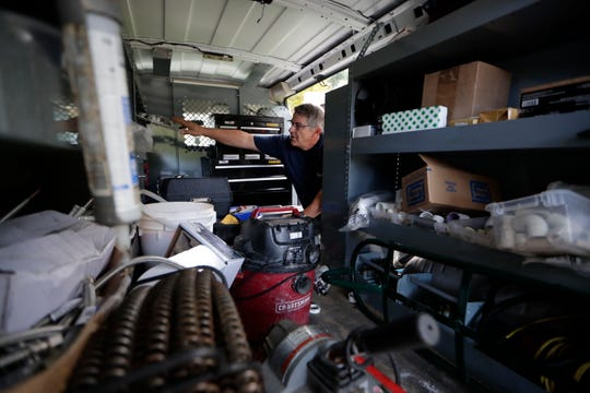 Jay Wolfe, a plumber with Capital Plumbing, digs through his van to find the tools needed to complete a plumbing issue at a customer's home.