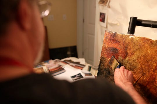Dean Gioia, a local painter, works on a scene consisting of trees and a path from a photograph he took.