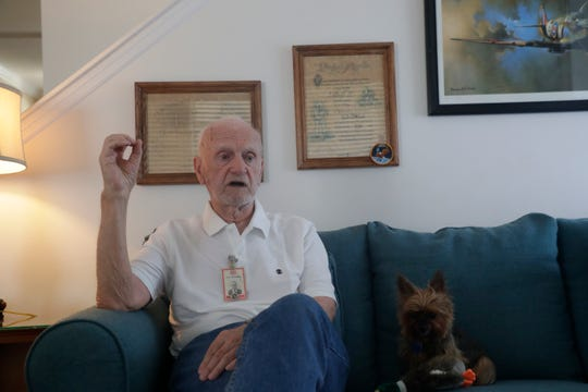 Duane Mitchell, 90, sits on his couch next to his dog Sophy, talking about his time working on rocket engines for Aerojet General and General Electric at the Kennedy Space Center.