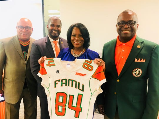 Marvalette Hunter holds up a football jersey she received as part of her donation to the program during the Willenium Tour in Houston. She stands alongside Thomas Jones, Jr. (far left), football coach Willie Simmons and FAMU NAA president Col. Greg Clark.