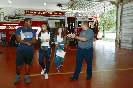Anthony Fitzpatrick, right, answers a few questions from St. Lucie County Boys & Girls Clubs members Jedd, Gabriella and Samara during a visit to St. Lucie Fire District's Station 12 in Port St. Lucie.